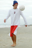 Boy playing beach soccer Stock Images