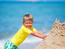 Boy playing on the beach Stock Images