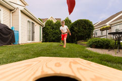 Boy playing bean bag toss in the backyard! royalty free stock images