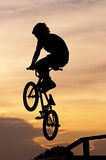 The boy playing Bicycle Stunts. Silhouette of the boy playing Bicycle Stunts Stock Images