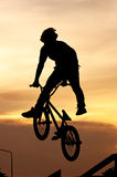 The boy playing Bicycle Stunts. Silhouette of the boy playing Bicycle Stunts royalty free stock photos