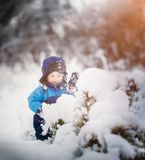 Happy caucasian child playing in snow Royalty Free Stock Photography