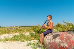 A boy is playing on a black clarinet sitting on an old wooden boat on the seashore and looking to the side, view from the side. royalty free stock photography