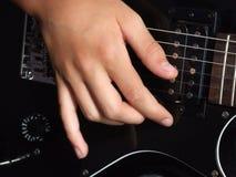 Boy playing black guitar. A hand shot of a young boy playing black guitar Stock Photo