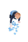 Boy playing blank puzzle game. Young boy doing blank puzzle isolated on white Stock Photos