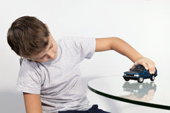 Boy playing with blue car on a glass table Royalty Free Stock Photography