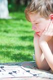 Boy playing board game. Young boy playing board game outdoor stock images