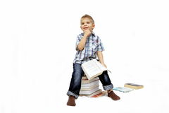 Boy playing with books. Little boy sitting on stack of books. Isolated over white Royalty Free Stock Images