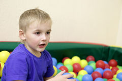 Boy playing in box of balls Stock Image