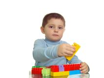 Boy playing with bricks looking to camera. Isolated Stock Photography