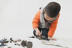 Boy playing bricks toy with instruction Royalty Free Stock Image