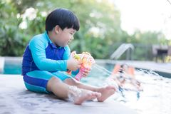 A boy is playing bubble gun boy is playing bubble gun the pool. A boy is playing bubble gun boy is playing bubble fish gun the pool Royalty Free Stock Photo