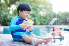 A boy is playing bubble gun boy is playing bubble gun the pool. A boy is playing bubble gun boy is playing bubble fish gun the pool Stock Image