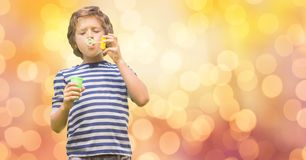 Boy playing with bubble wand over bokeh Royalty Free Stock Photography