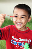 Boy Playing Bubbles. A young boy enjoying his time playing bubbles in the garden Stock Images