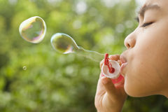 Boy Playing Bubbles. A young boy enjoying his time playing bubbles in the garden from side view Royalty Free Stock Images