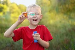 Boy playing with bubbles. Cute little boy playing with bubbles in summer park Royalty Free Stock Photo