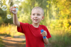 Boy playing with bubbles. Portrait of a cute little boy playing with bubbles in summer park Stock Photo