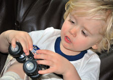 Children's Playtime. Blond young boy playing with a toy truck, close-up Stock Image