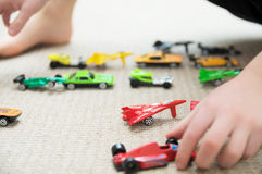 Boy playing with car collection on carpet.Child hand play. Transportation, airplane, plane and helicopter toys for children Stock Photos