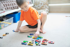 Boy playing with car collection on carpet.Child play home. Transportation, airplane, plane and helicopter toys for children. Miniature models royalty free stock photography