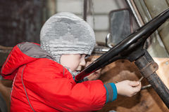 Boy playing in the car. Boy puts the key into the ignition lock, playing in the old car, focus on the hand with key Stock Image
