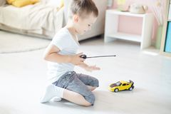 A boy playing with a car remote. In the room stock photography