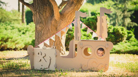 Boy playing in cardboard boat at park. Stock Photos