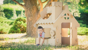 Boy playing in cardboard house Royalty Free Stock Images