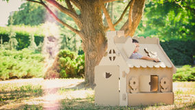 Boy playing in cardboard house Royalty Free Stock Photography