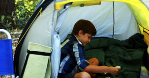 Boy playing cards in the tent. At campsite stock video