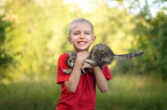 Boy playing with cat. Cute little boy playing with cat in summer park Royalty Free Stock Photos