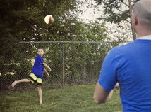 Boy Playing Catch with Dad. A young men plays catch with his Dad in the backyard royalty free stock photography