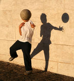 Boy playing catch with his shadow. Near the wall. Lisbon, Portugal Stock Photography