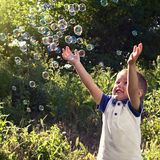 Boy playing catch soap bubbles outdoors Royalty Free Stock Photography