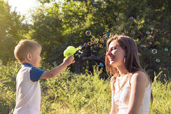 Boy playing catch soap bubbles outdoors Stock Photography