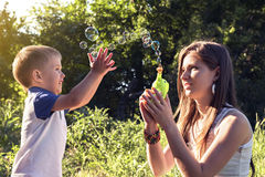 Boy playing catch soap bubbles outdoors Stock Images