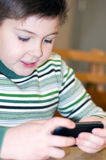 Boy playing on  cell phone Royalty Free Stock Photos