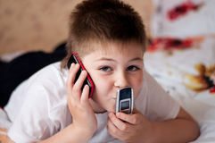 Boy playing on cell phones Stock Images