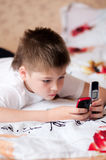 Boy playing on cell phones Stock Photos