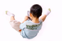 Boy playing with cellphone. Picture of a little chinese boy playing with cellphone sitting on the ground Royalty Free Stock Photography