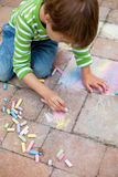 Boy playing with chalk on pavement Stock Image