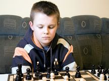 Boy playing chess. A young teenager playing chess, thinking hard Stock Images