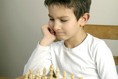 Boy playing chess Stock Images