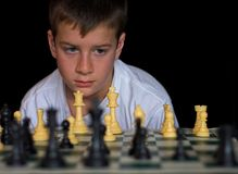Boy Playing Chess. On black background Royalty Free Stock Photos