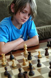 Boy playing chess. A boy studying his moves during a chess game royalty free stock photo