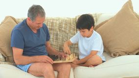 A boy playing chess with his grandfather. On the sofa stock video footage
