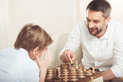 Boy playing chess together with smiling father at home. Little boy playing chess together with smiling father at home Stock Photos