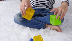 The boy is playing with colored blocks, sitting on the floor in the room. Happy children, development.