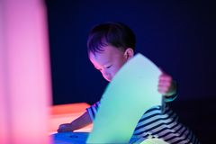 A boy is playing colorful light cubes. In the dark study room Royalty Free Stock Image
